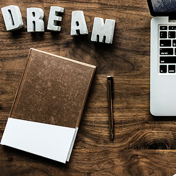 Notepad, pen, laptop, and letters spelling 'DREAM' all sitting on a desk